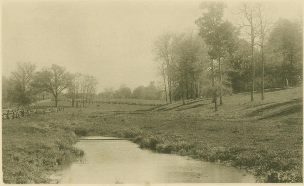 Black and white photograph showing Dunn Meadow and the Campus River