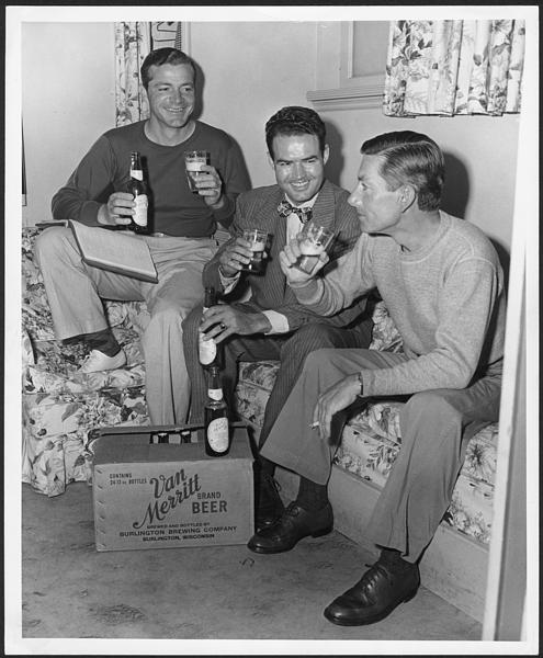 Hoagy Carmichael sitting on a sofa drinking Van Merritt beer with Dana Andrews (left) and another unidentified man.