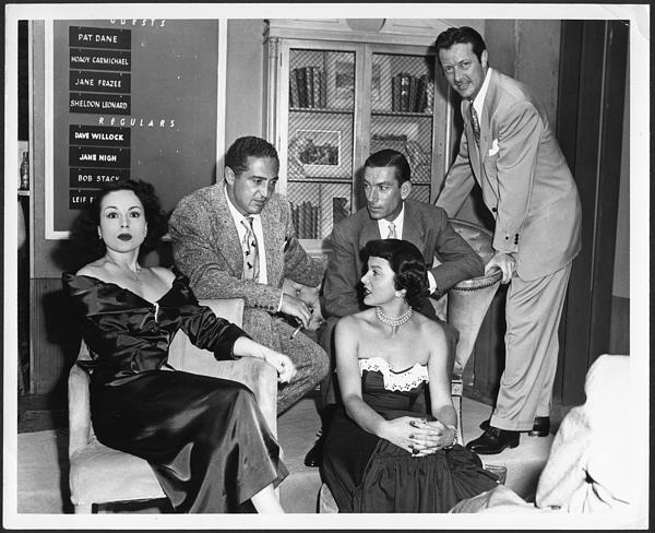 Pat Dane (far left), Sheldon Leonard (2nd from left), Hoagy Carmichael, Jane Frazee, and Bob Stack (standing) on the set of the Pantomime Quiz Time Show, July 22, 1949. [negative 12/28]