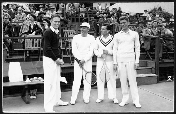 Hoagy Carmichael with three unidentified men on a tennis court with spectators in the background.