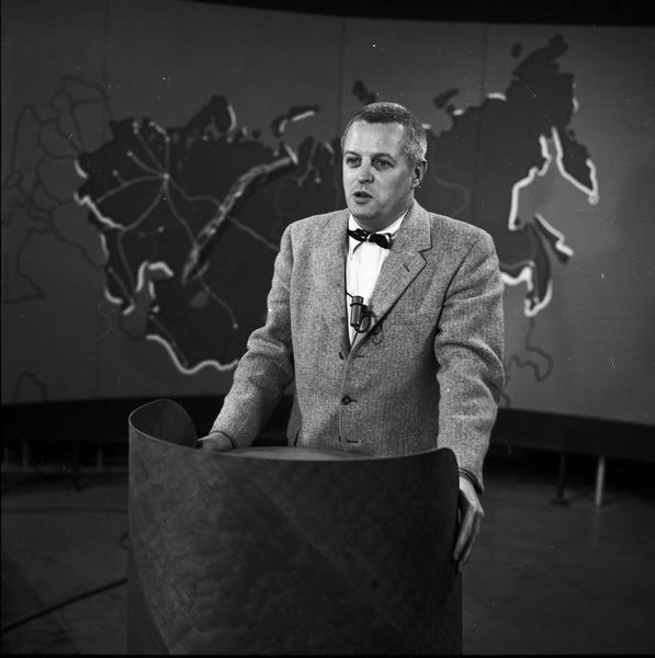 Robert Byrnes on television set, standing at lectern