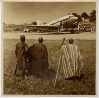Three men in traditional dress watch airplane and crowd from distance