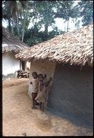 Children pretending to apply new coat to mud house
